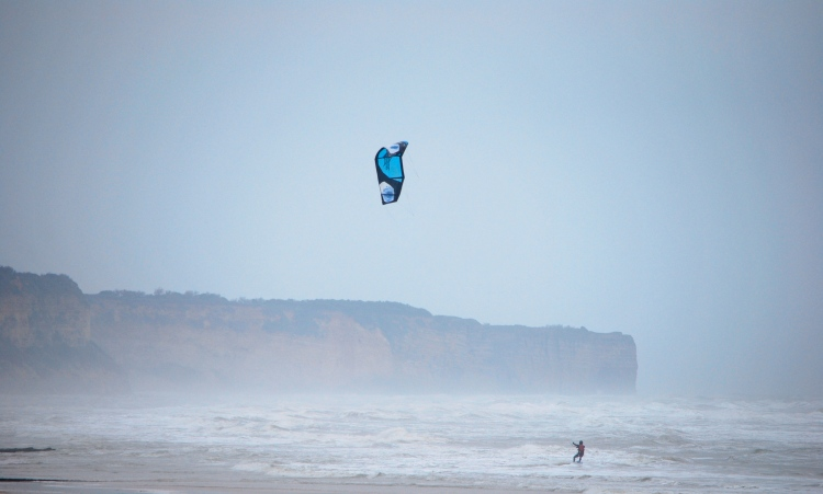 Windsurfer with le Pointe du Hoc clifftop in the background